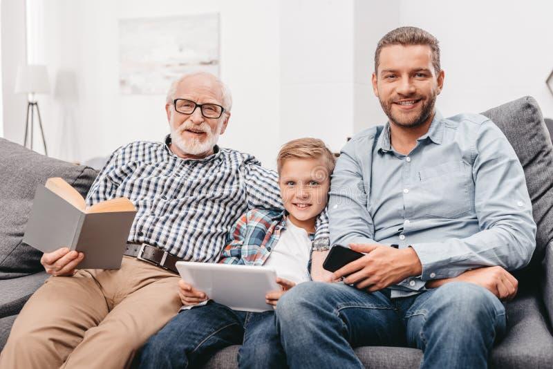 Pai, filho e avô relaxando junto no sofá na sala de visitas com tabuleta digital, smartphone fotos de stock