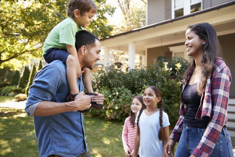 Pai Gives Son Ride em ombros como a casa da licença de família fotografia de stock