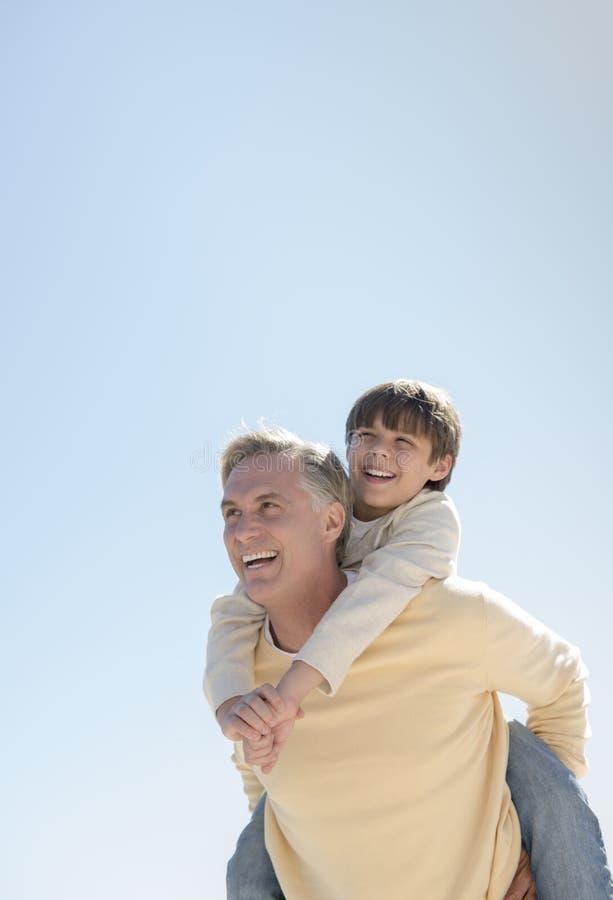 Pai Giving Piggyback Ride ao filho contra o céu azul claro imagens de stock royalty free