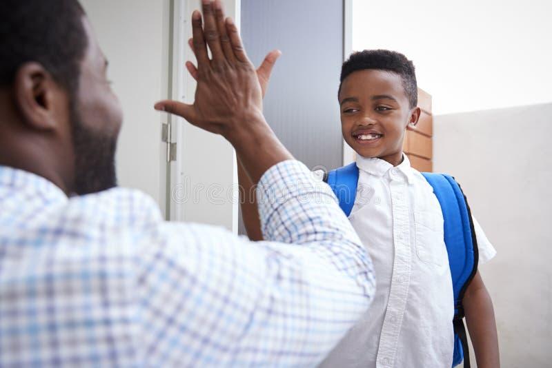 Pai Giving Son High cinco como sae para a escola imagens de stock