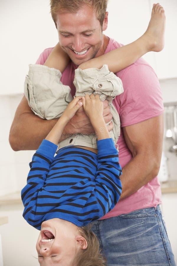Pai Holding Son Upside para baixo em casa imagens de stock