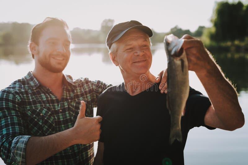 Pai idoso com pesca farpada do filho no rio imagens de stock