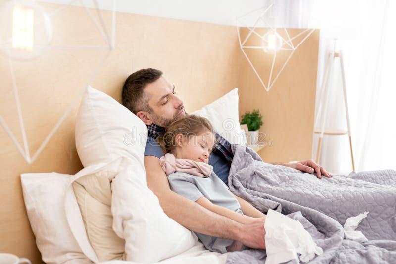 Pai insalubre e filha que dormem junto fotos de stock