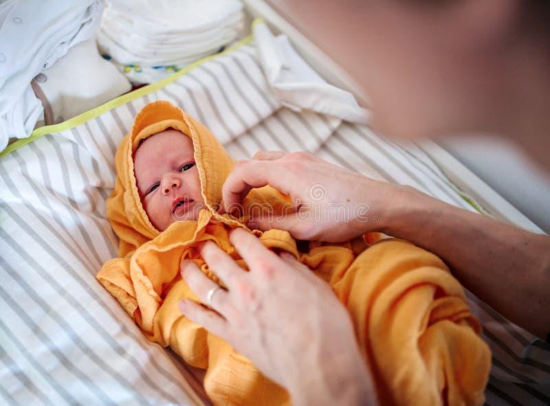 Pai irreconhecível que seca um bebê recém-nascido com uma toalha após o banho em casa imagens de stock royalty free