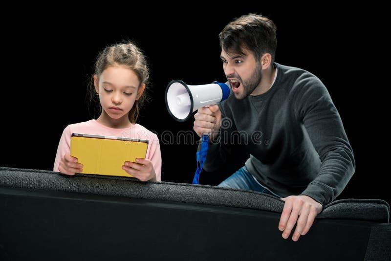 Pai irritado com megafone que grita na filha da virada que usa a tabuleta digital fotografia de stock royalty free