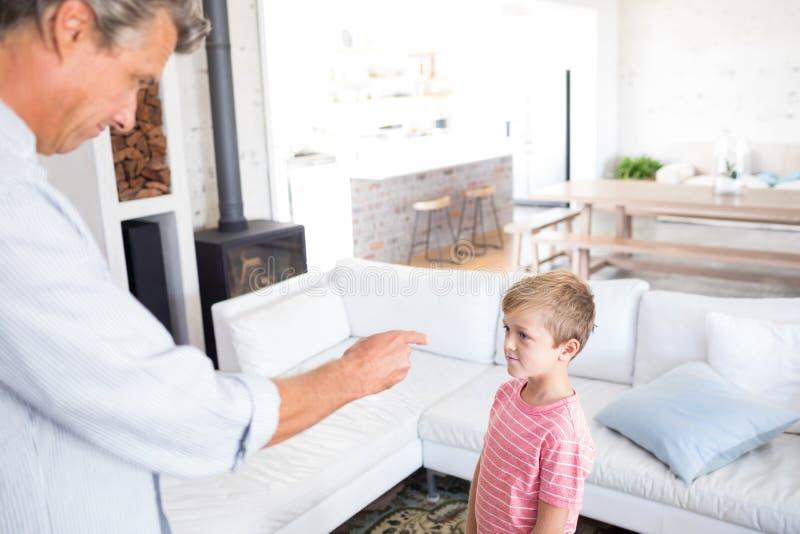 Pai irritado que discute seu filho na sala de visitas foto de stock royalty free