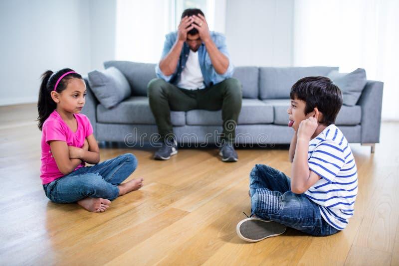 Pai irritado que senta-se no sofá quando luta das crianças imagem de stock