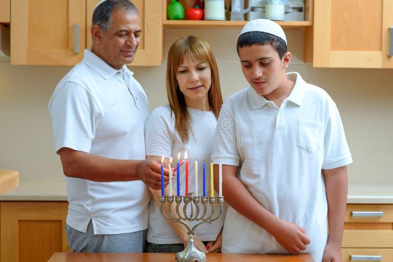 Pai judeu, mãe e filho adolescente acendendo as velas de Chanukkah em uma menorah por feriados foto de stock