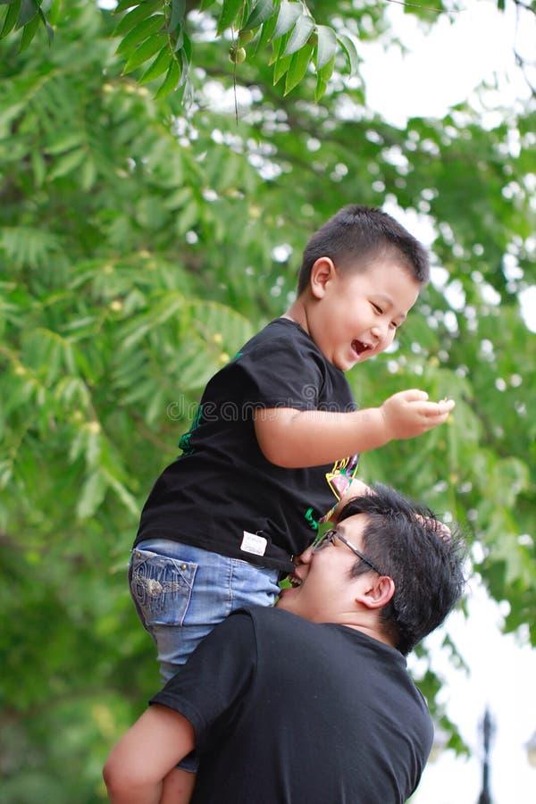 Pai latino-americano e filho que têm o divertimento no parque fotos de stock