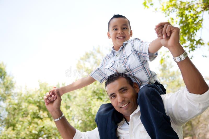 Pai latino-americano e filho que têm o divertimento no parque imagens de stock royalty free