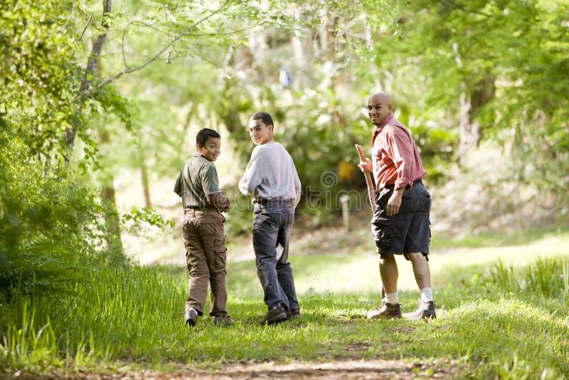 Pai latino-americano e filhos que caminham na fuga nas madeiras fotografia de stock