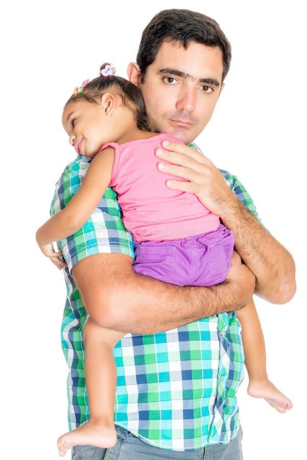 Pai latino-americano sério que leva sua filha pequena cansado imagem de stock royalty free