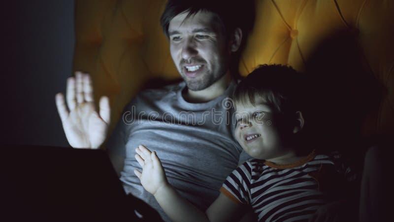 Pai loving e seu filho pequeno que têm o bate-papo video em linha com as avós que usam o tablet pc e ao encontrar-se na cama imagem de stock royalty free