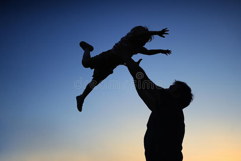Pai loving e seu filho pequeno que têm o fã junto fora Família como a silhueta no por do sol foto de stock royalty free