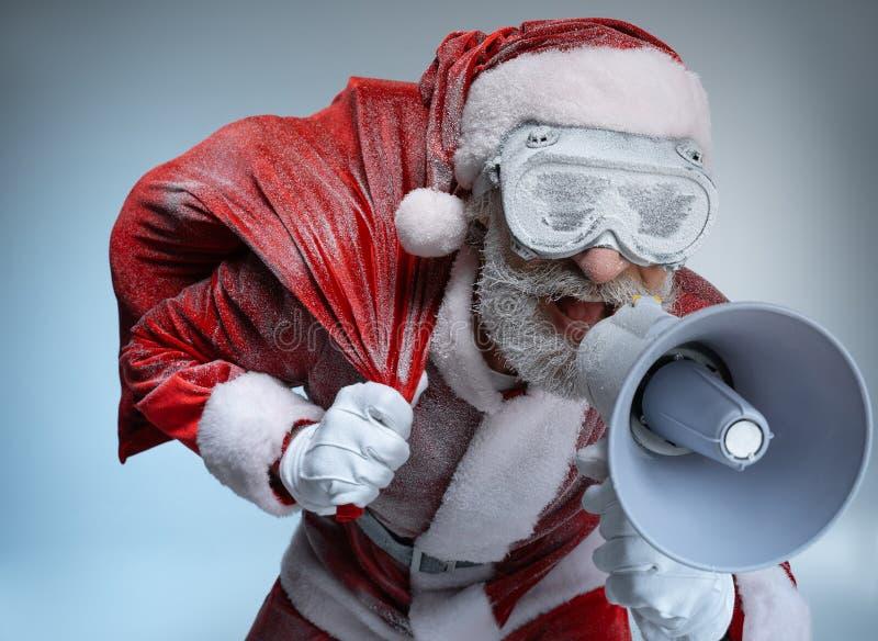 Pai Natal idoso com saco falando em megafone fotografia de stock royalty free