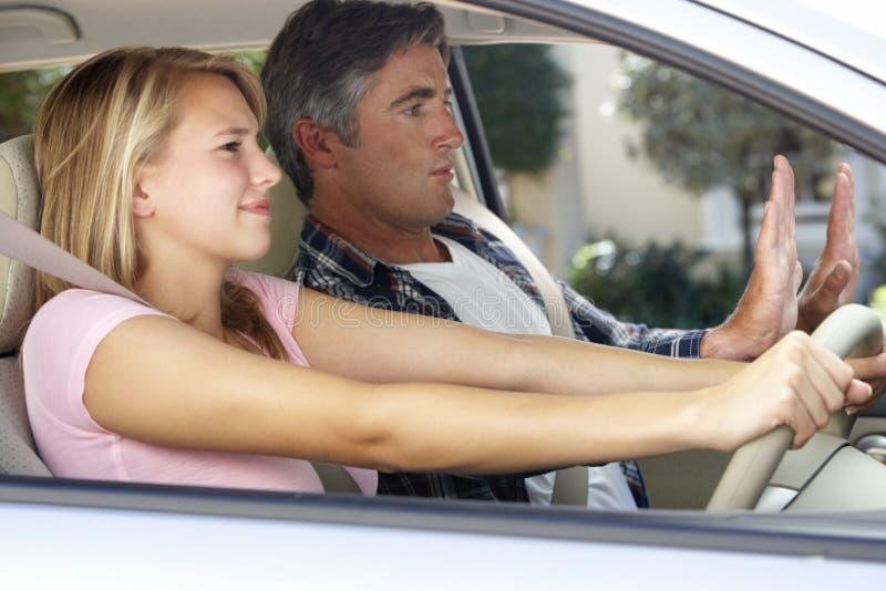 Pai nervoso Teaching Teenage Daughter a conduzir imagem de stock royalty free
