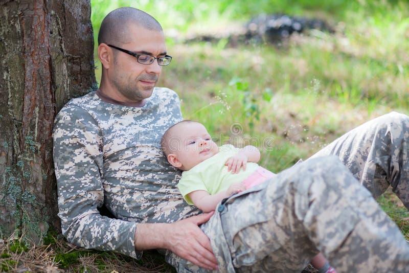 Pai no uniforme da camuflagem e seu bebê fotos de stock royalty free