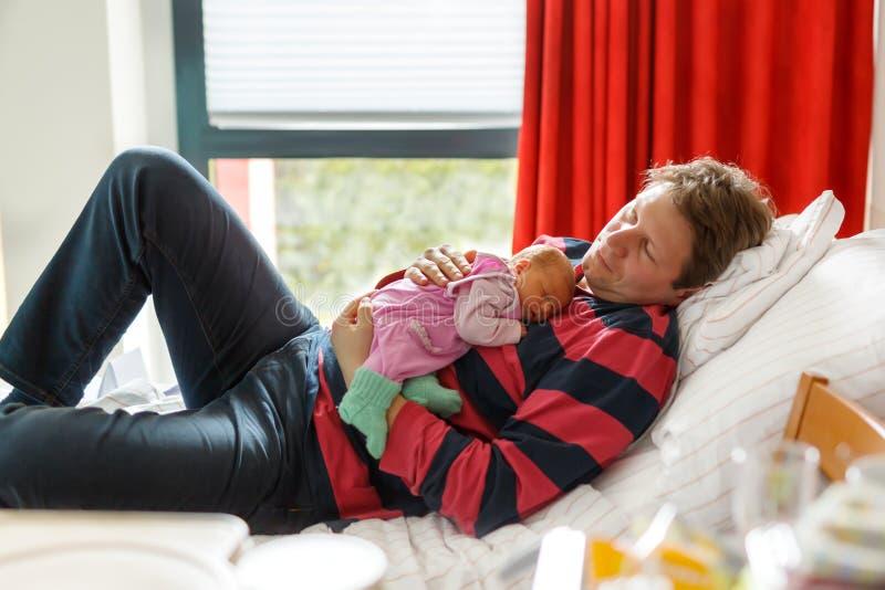 Pai novo cansado que guarda sua filha recém-nascida de sono do bebê nos braços no hospital imagem de stock royalty free