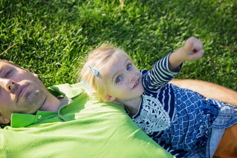 Pai novo com a filha do bebê que encontra-se na grama em um parque fotografia de stock royalty free