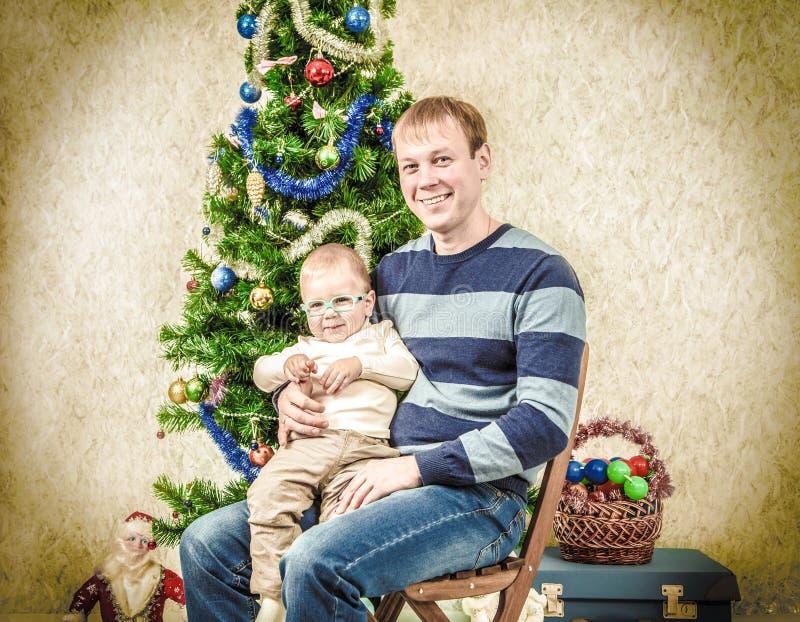 Pai novo com o menino engraçado perto do abeto do ano novo Estilo do vintage foto de stock