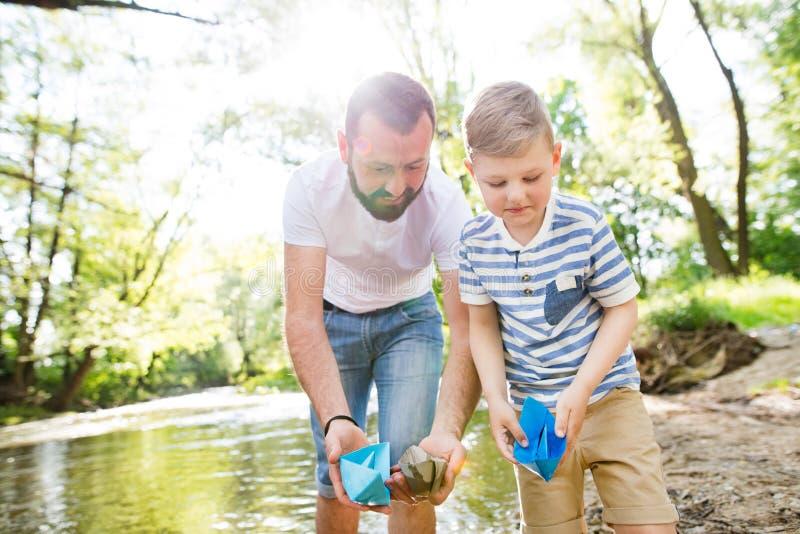 Pai novo com o rapaz pequeno no rio, dia de mola ensolarado foto de stock