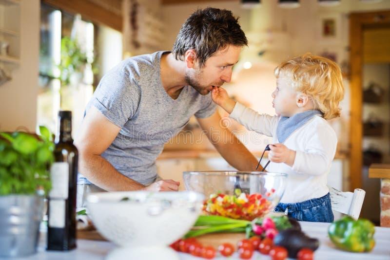 Pai novo com um cozimento do menino da criança imagens de stock