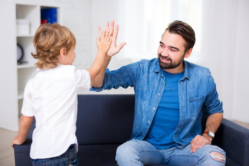 Pai novo considerável que dá uns cinco altos a seu filho pequeno fotografia de stock