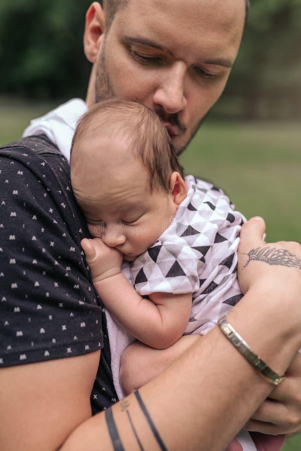 Pai novo de inquietação que embala seu bebê adorável fora imagem de stock royalty free