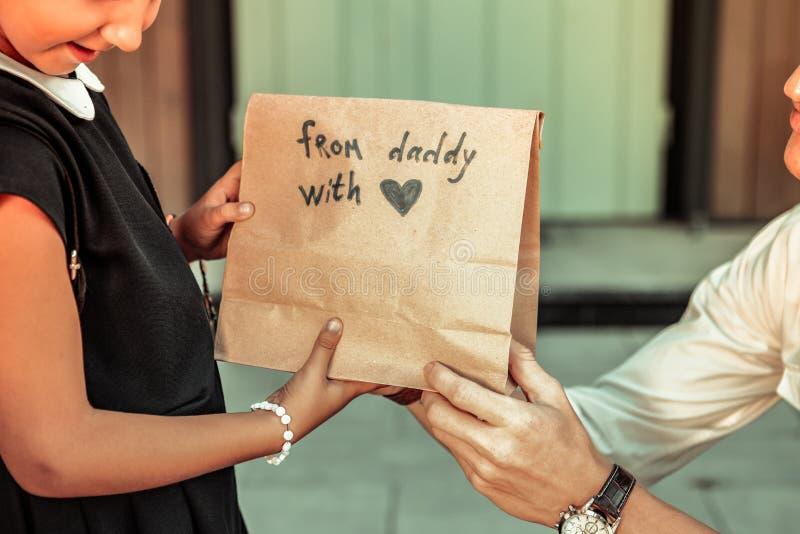 Pai novo de suporte que dá pouco pacote da filha com almoço fotografia de stock