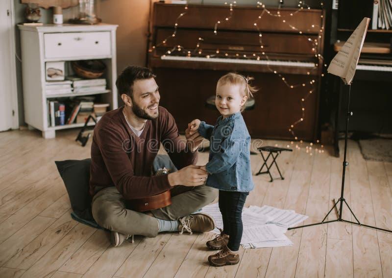 Pai novo e filha pequena que jogam a guitarra acústica imagem de stock