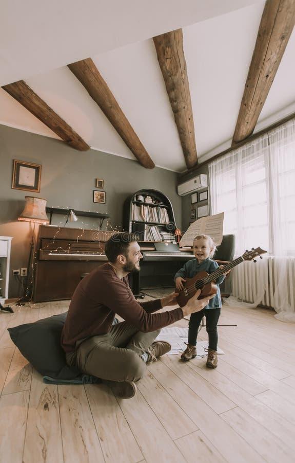 Pai novo e filha pequena que jogam a guitarra acústica foto de stock royalty free
