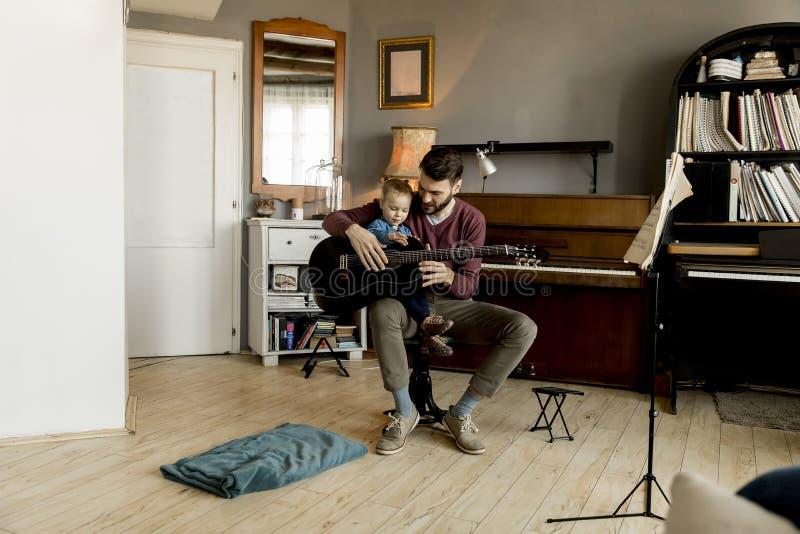 Pai novo e filha pequena que jogam a guitarra acústica foto de stock