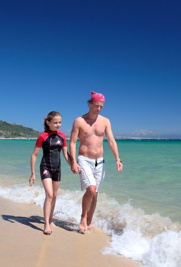 Pai novo e filha que andam ao longo da praia ensolarada imagem de stock royalty free