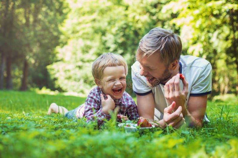 Pai novo e seu filho que comem morangos no parque Piquenique Retrato ao ar livre imagens de stock royalty free