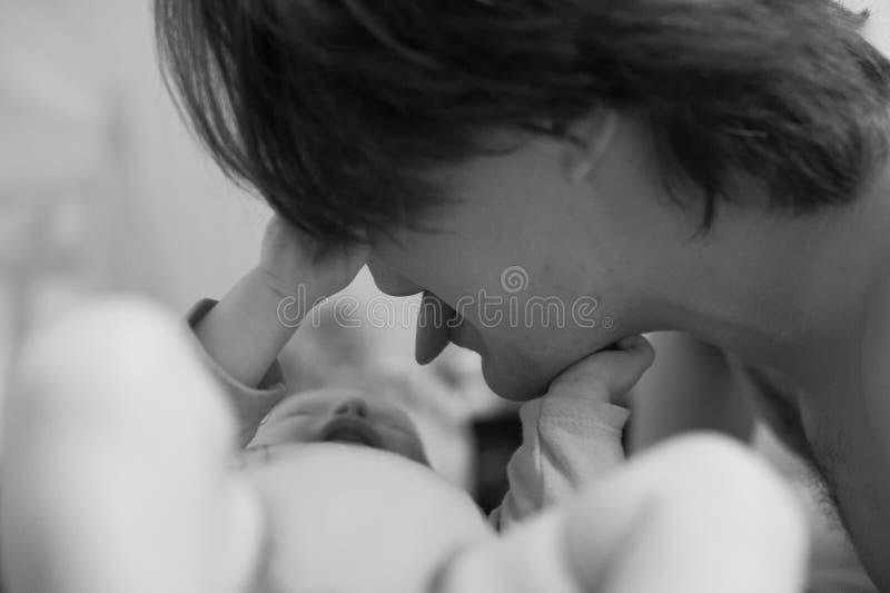 Pai novo enganado com seu bebê pequeno O paizinho joga com sua filha e mostra-lhe a língua Tonning preto e branco fotografia de stock royalty free