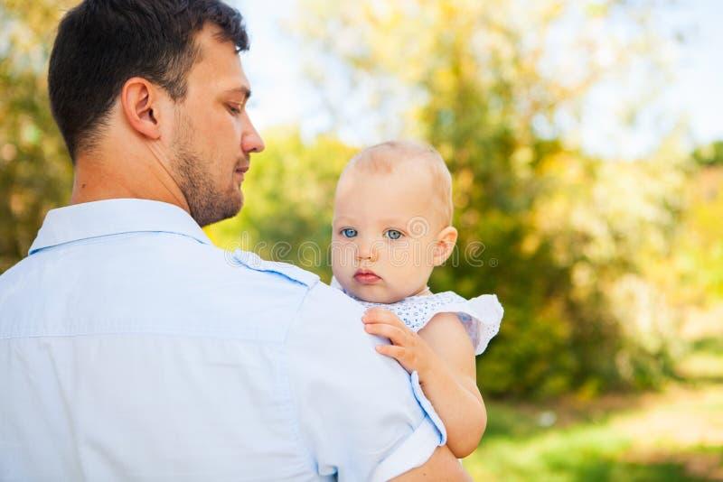 Pai novo feliz com a criança que passa o tempo exterior em um verão imagem de stock