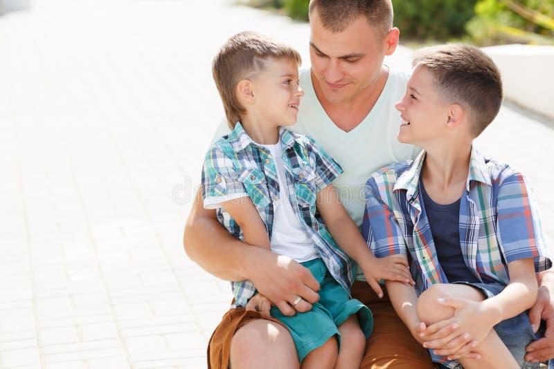 Pai novo feliz com seus dois filhos fotografia de stock