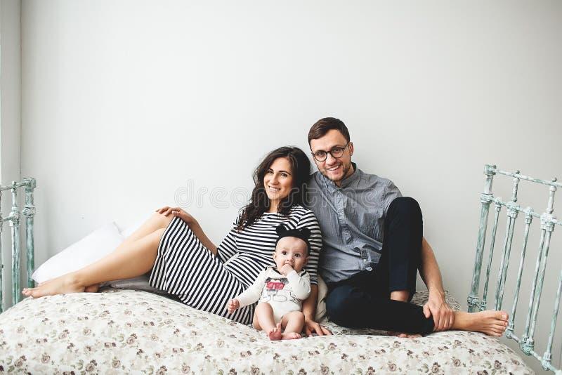 Pai novo feliz, mãe e bebê bonito encontrando-se na cama rústica foto de stock royalty free