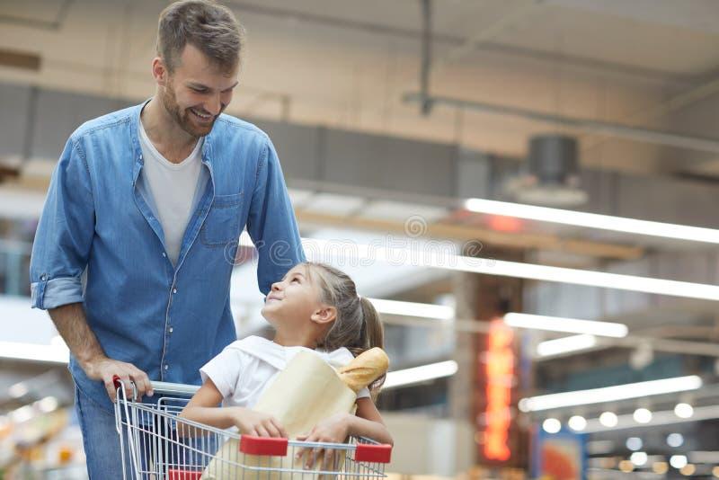 Pai novo feliz no supermercado imagem de stock