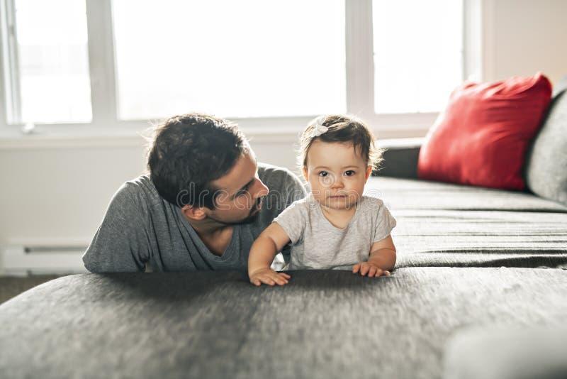 Pai novo feliz que joga com a filha pequena no sofá foto de stock royalty free