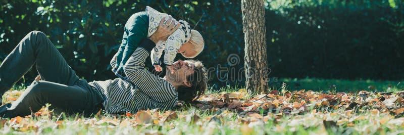 Pai novo feliz que joga com seu filho foto de stock
