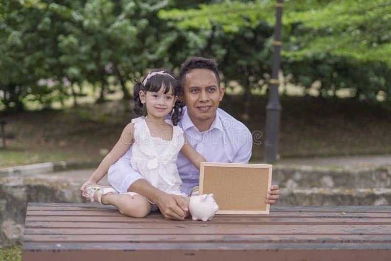 Pai novo para ensinar sua filha ao dinheiro de salvamento no mealheiro para o melhor futuro imagens de stock royalty free