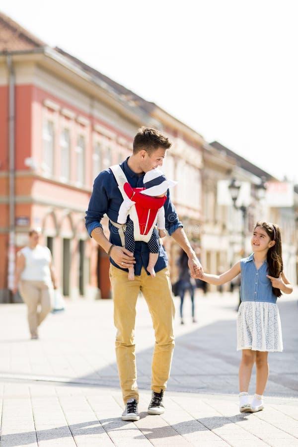 Pai novo que anda com as filhas bonitos na rua imagens de stock