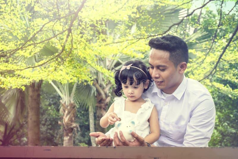 Pai novo que ensina sua filha começar salvar o dinheiro sobre o na imagem de stock royalty free