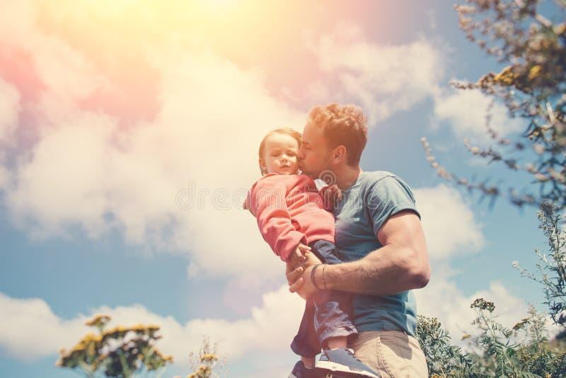 Pai novo que guarda e que beija sua filha bonito, ao passar o tempo fora fotografia de stock