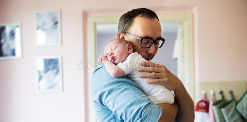 Pai novo que guarda o filho recém-nascido do bebê em seus braços foto de stock royalty free