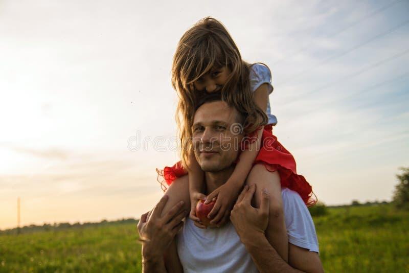 Pai novo que guarda pouca filha e que está no campo verde fotografia de stock