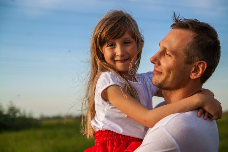 Pai novo que guarda pouca filha e que está no campo verde foto de stock royalty free