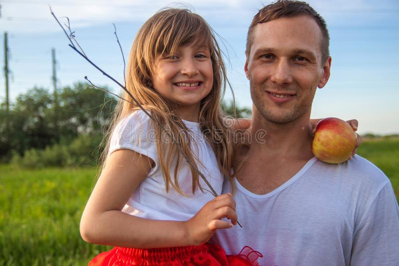 Pai novo que guarda pouca filha e que está no campo verde foto de stock