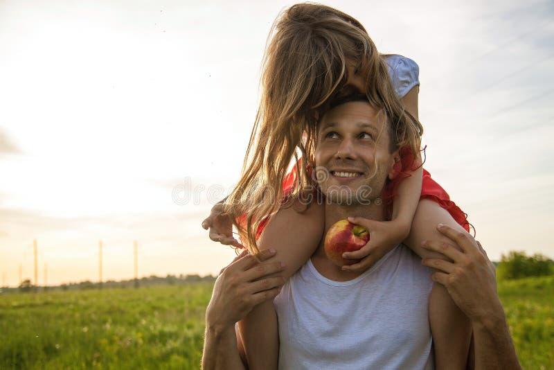 Pai novo que guarda pouca filha e que está no campo verde imagens de stock